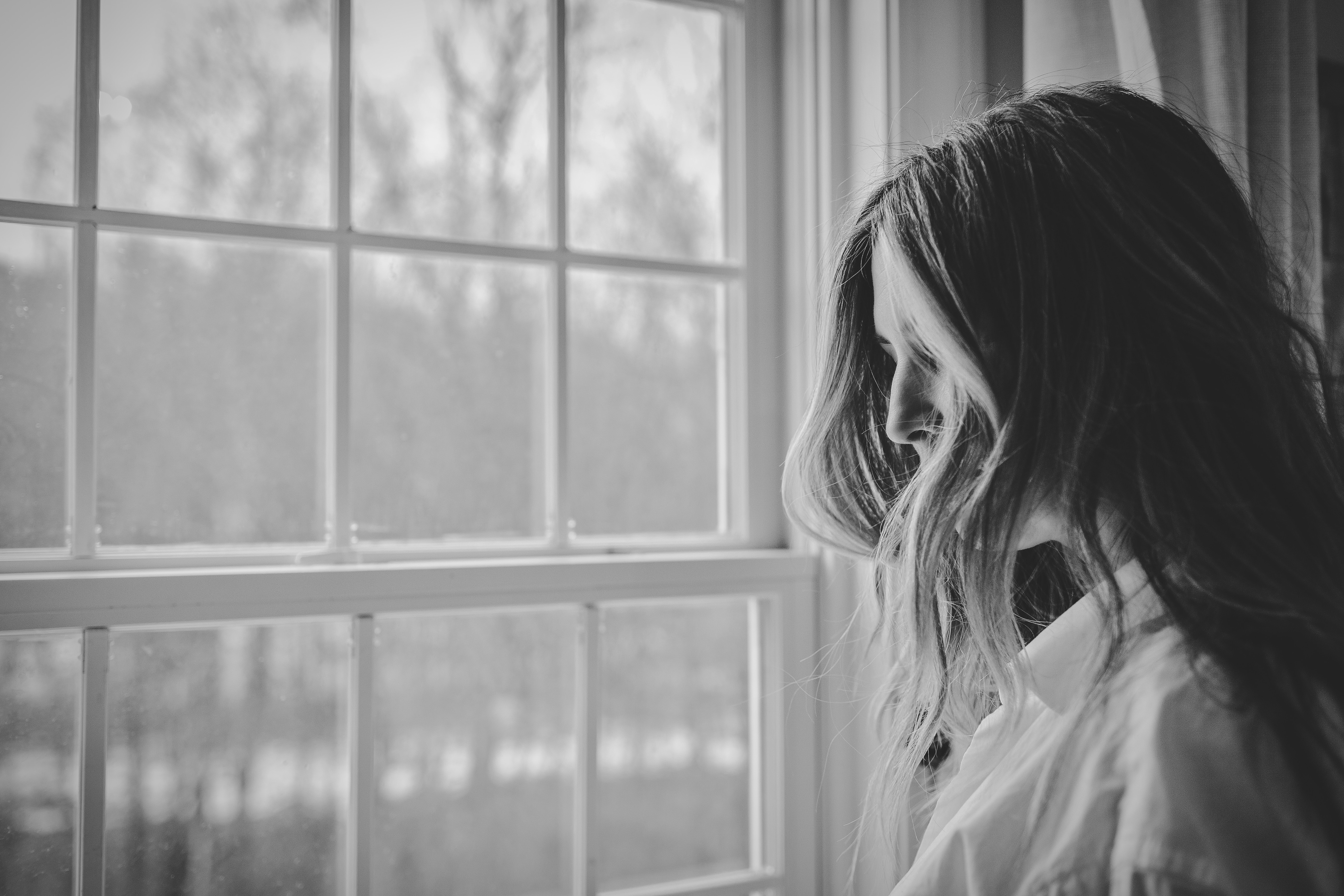 black and white. woman with face hidden by her hair looking out a window