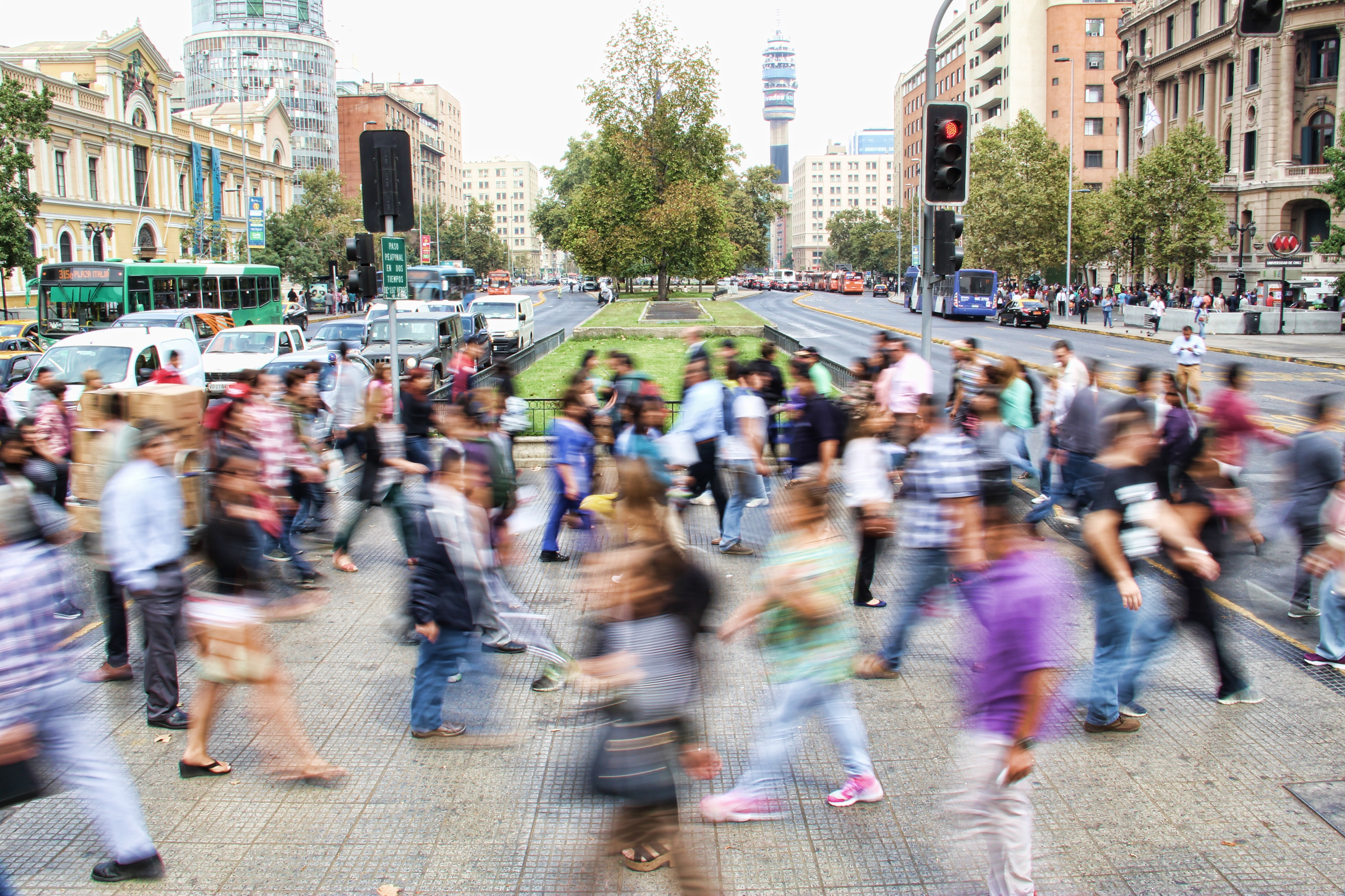 a blur of people rushing across a busy, city street
