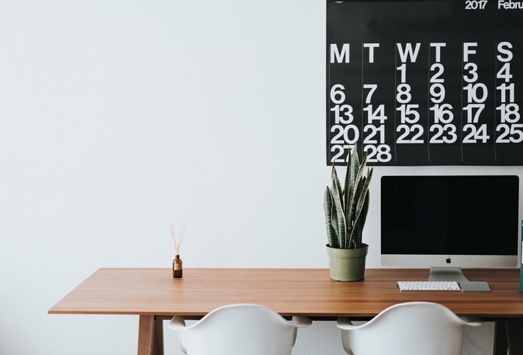 brown table with a computer screen, two white chairs, a small plant, and black calendar with white numbers on the wall