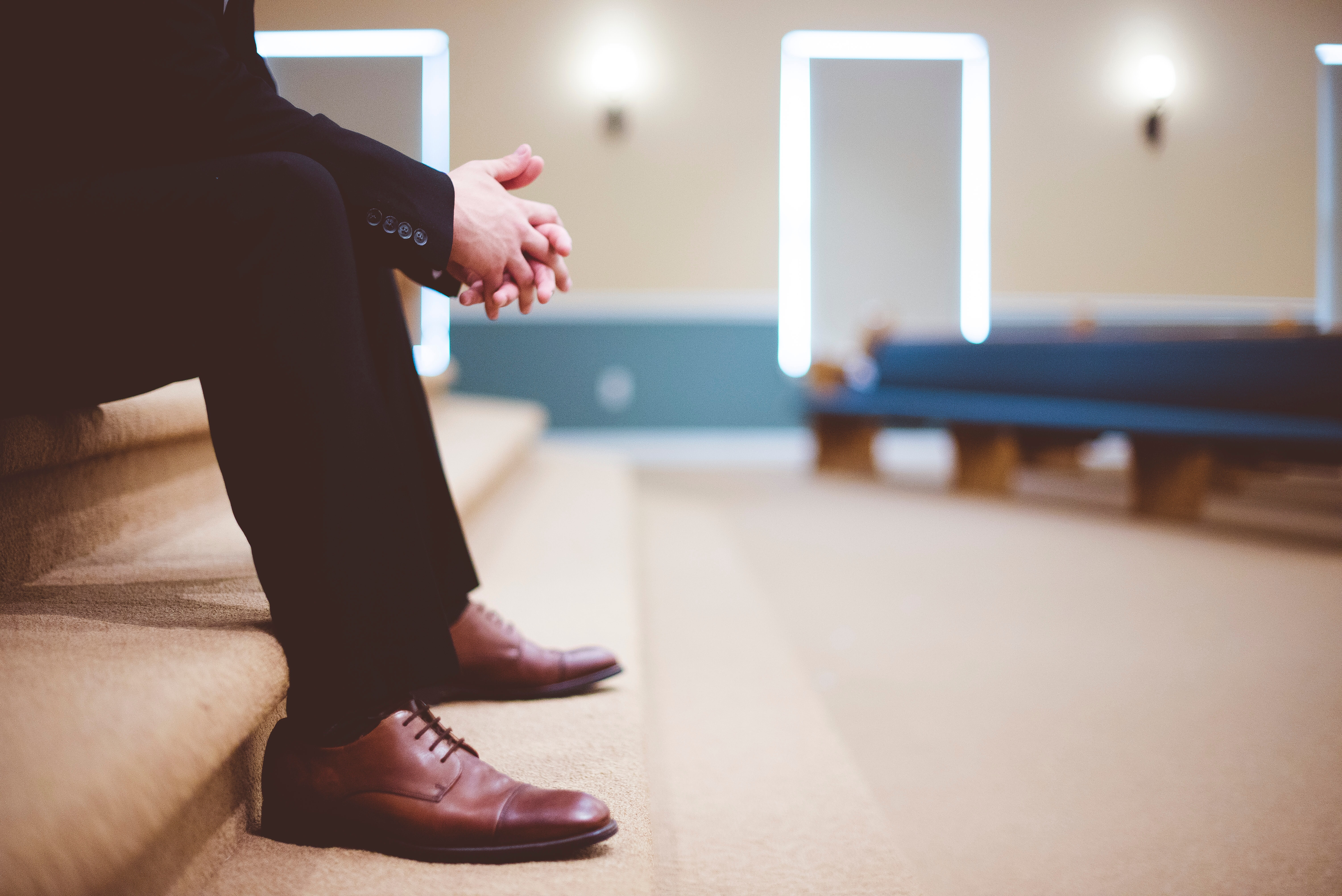 man in suit and dress shoes sitting on alter steps of a church. empty church pews in the background
