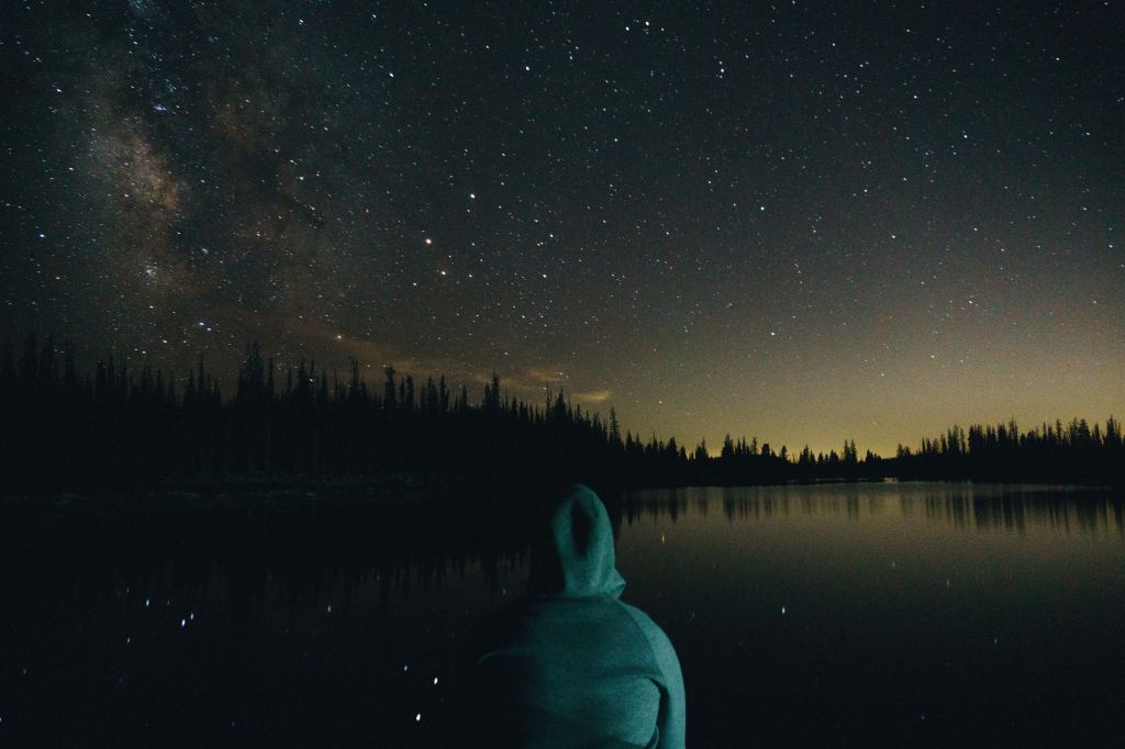 person in hoodie looking at a starry sky